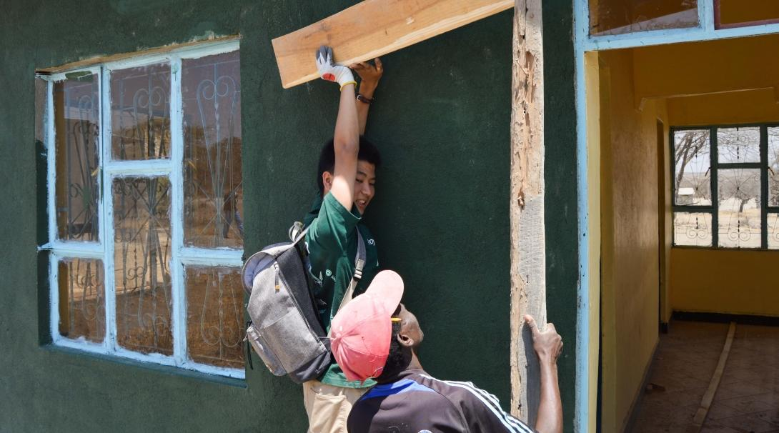 Male Culture and Community Volunteer helps build a house for teachers at a school holding a peice of wood during a volunteering project in Tanzania.